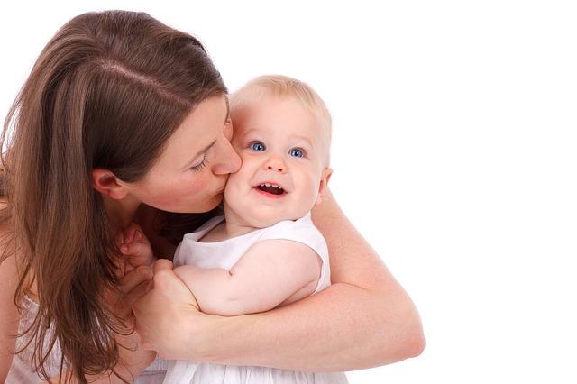 mama całuje w policzek swoje dziecko
