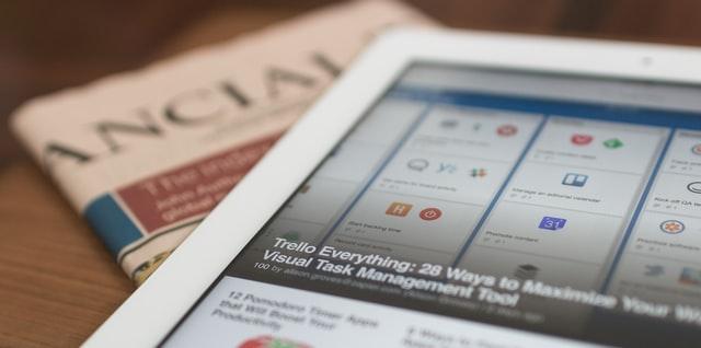 tablet i gazeta finansowa na stole